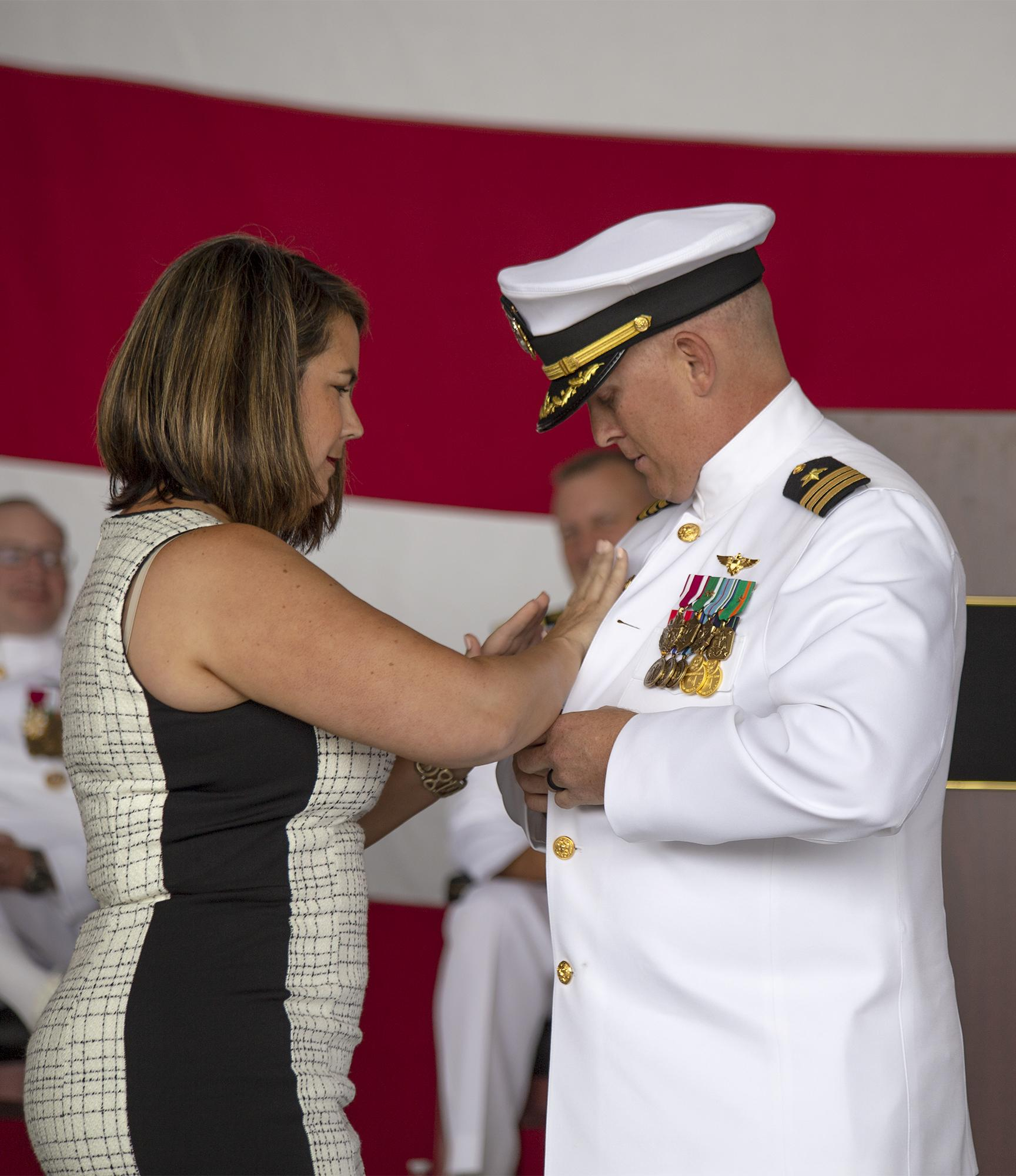 Cmdr. Paul Meyer receives his command pin from his wife