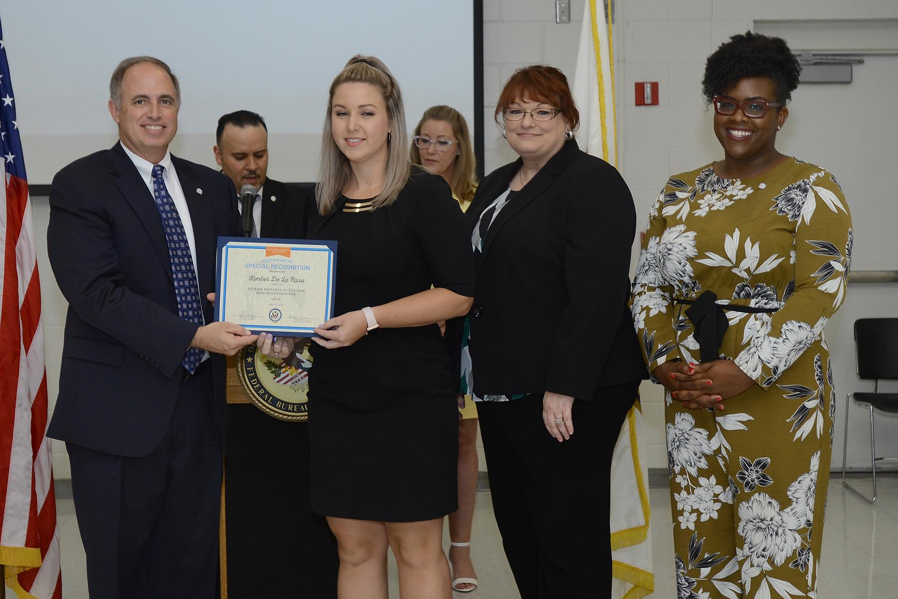 John J. Daly, President of the Central Florida Federal Executive Association presents NAWCTSD Management Analyst, Kimber De La Rosa with the association's Federal Employee of the Year Honorable Mention in the Valor Category.