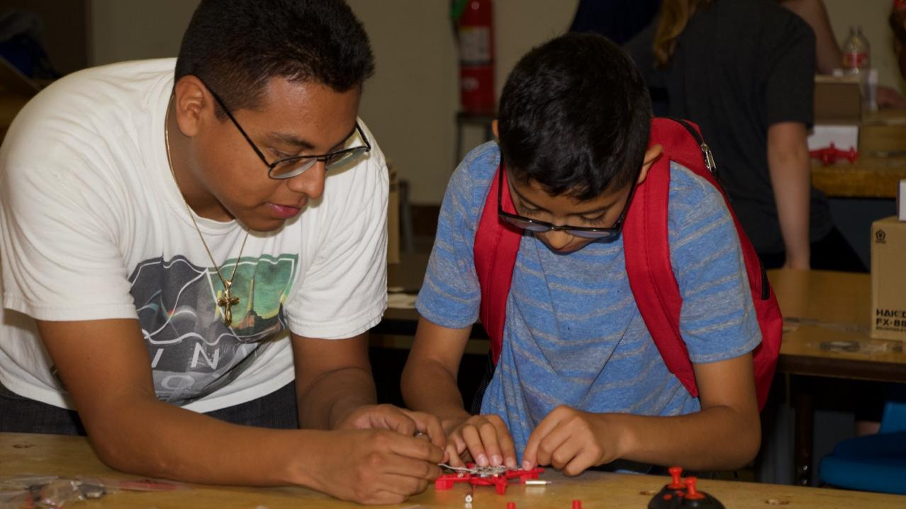 Kenn Hernandez, an electrical engineer at Naval Air Warfare Center Weapons Division, helps a student build a drone during a four-day coding camp in Ridgecrest, California on June 3-6. (U.S. Navy photo by Paul Kakert)