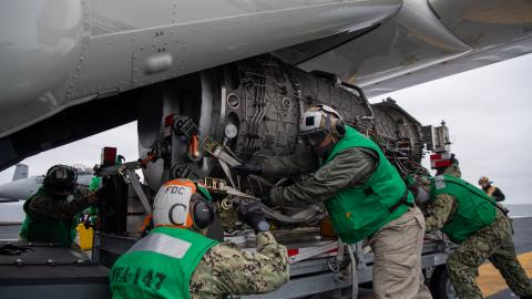 Strike Fighter Squadron (VFA) 147 load an F-35C engine module onto a CMV-22B Osprey with Fleet Logistics Multi-Mission Squadron (VRM) 30