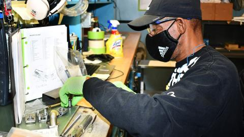 Man sorts parts on workbench