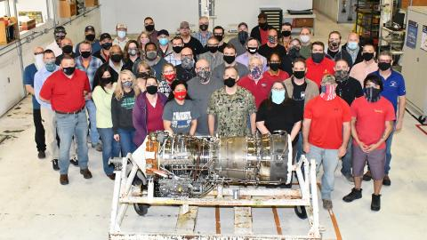 Group of aircraft workers poses for group photo behind T64 engine